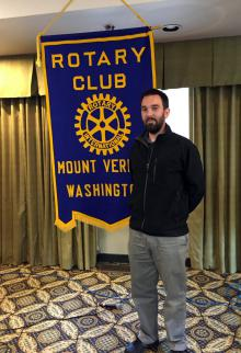 Steven Kreft Standing next to a Rotary Club sign.